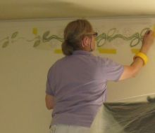 Female in the process of stencilling on a white wall
