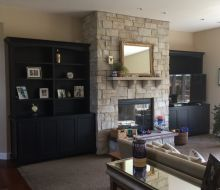 family room with fireplace flanked by black paonted built-in shelves