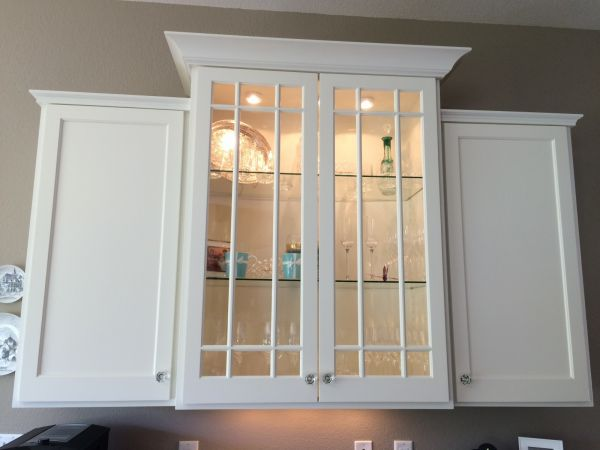 Four painted white upper kitchen cabinets. 2 solid doors and 2 glass doors with lit interior