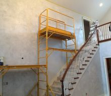 yellow scafolding on a stairway with light blue walls