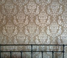 Brown wall i bedroom with lighter color stencil design