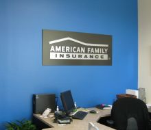 Interior of American Family Insurance office. Blue and gray walls with business logo.
