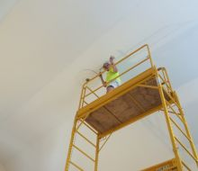 Female painter standing on 3 levels of yellow scaffolding painting a 2.5 story ceiling in light blue.