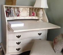 White painted secretary desk in a pale blue bedroom. Leaf is down with lamp