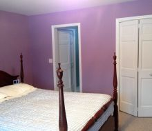 bedroom with lavendar walls and white trim